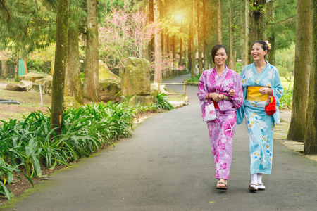 beautiful girlfriends traveler women wearing japanese kimono clothing together and walking on tree path in japan cherry blossoming sakura park at sunlight afternoon.