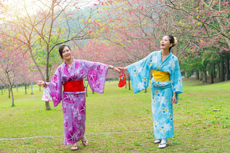 happy pretty girlfriends hand in hand joyful cheerful together and dressing traditional japan kimono walking on sakura blooming park enjoying summer sunny day during travel vacation. 版權商用圖片