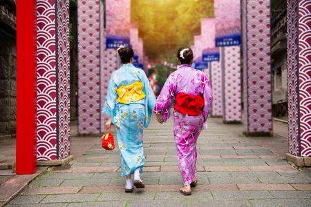 kimono japan young girls join Japanese local festival together walking on the local history culture pathway in Japan on summer vacation at sunny day with traditional clothing dress.
