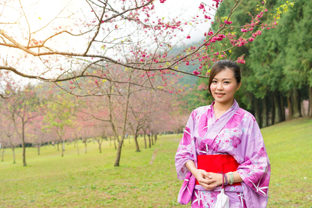 smiling beauty woman visiting blooming cherry flower trees park in japan and wear traditional japanese kimono clothing taking picture with sakura on spring travel vacation.