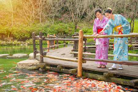 beautiful Japanese woman dressing kimono at sakura garden park enjoying watching much carp fish in front of water pond on the wood path and pointing copyspace with best girlfriend. Stock Photo - 83632993