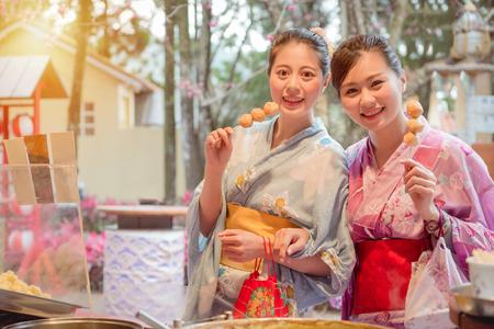 Aziatische Chinese vriendinnen reizen in Japan eten gebakken gehaktballen spiesje samen op de plaatselijke winkel van het eten en gekleed in kimono in de middag met zonneschijn in vintage retro film kleur. Stockfoto