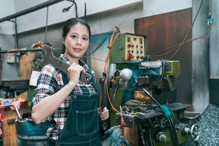 smiling lathe factory worker looking at camera when she ready to using large wrenches repair working milling machine device. Reklamní fotografie