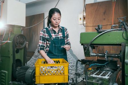 professionele draaibank fabriek vrouwelijke manager die naar het product kijkt en alle componenten controleert, heeft gelijk wanneer zij op de verwerkingsafdeling voor freesmachines werkt. Stockfoto