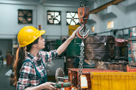 beautiful young industry factory female worker adjusting chain cranes machining when she ready to transport lathe finished products.