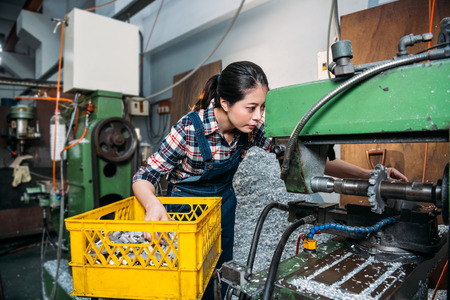 young lathe female worker looking closely at machine and put in yellow basket parts components seriously working in milling machine factory processing area.