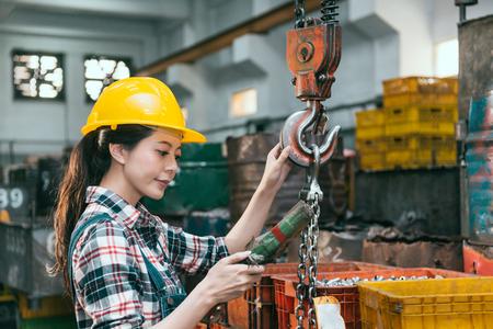 BERZEugter eleganter Fräsmaschine Fabrikarbeiter, der einen Helm trägt und die Fernbedienung mit Kettenkran einstellt, um das Fertigprodukt der Komponenten zu versenden. Standard-Bild - 83698390