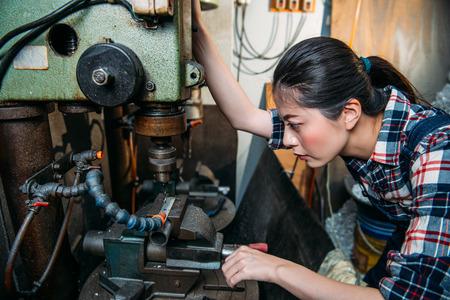 매력적인 구성 요소 공장 여성 직원 공장 밀링 기계 부서에서 작업 드릴링에 대 한 산업용 기계를 조정합니다.