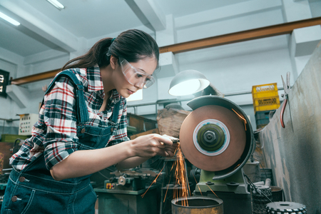young beautiful milling machining worker using abrasive wheel tool grinding metal components . Banque d'images