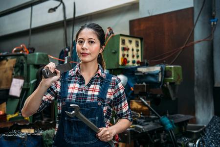 두 개의 큰 렌치를 들고 젊은 산업 공장 여자 밀링 머신 공장에서 카메라 서 자신감이 웃는 얼굴. 스톡 콘텐츠