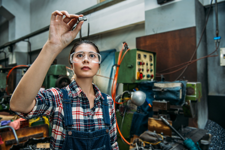 beautiful milling machine female staff wearing safety goggles focus on components finished product standing in front of technology machine. Standard-Bild