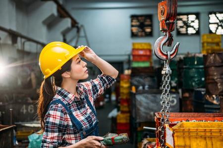真剣に部品工場の女性スタッフはヘルメット チェーン クレーンを見て焦点を保持し、配信完成品リモコンを調整します。 写真素材