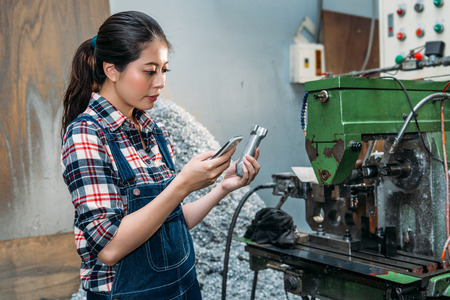 pretty milling machine female staff holding factory finished product and using mobile phone to check design ensure correctness in drilling sector work area.
