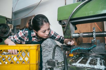 mooie mooie meisjewerkster die in het malen machinaal bewerkend werkt de fabriek en het verwerkende bedrijf componenten met automatische machines.