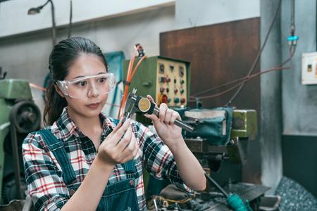 젊은 매력적인 밀링 가공 여성 노동자 안전 안경을 입고 선반 공장에서 작업 하 고 캘리퍼스 규모 장치 제조 정확도 부품 정확도를 사용 하여.