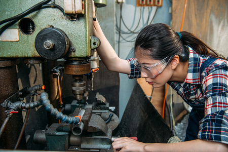 seriously industrial factory woman wearing safety protection glasses focus on adjusting machine and looking at drilling position in milling machine working area.