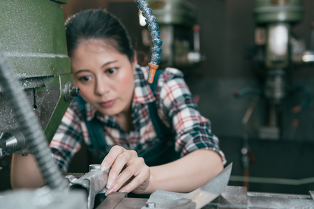 professional milling machining female employee put steel parts into automatic machine and drilling in factory processing working space. selective focus photo. 版權商用圖片