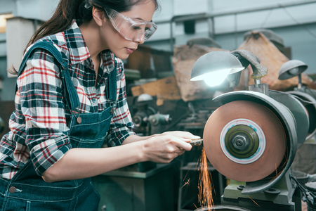 beauty pretty female lathe company employee wearing safety goggles to grind steel product and using abrasive disc machine working.