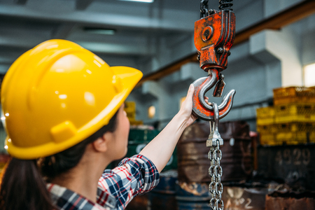 confident industrial factory woman holding chain crane and bring up parts products ready transport shipments with selective focus photos. Stok Fotoğraf - 83698429
