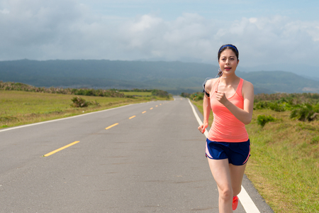 slim beautiful woman every morning sporting to running on a clean road listen to music training the body efforts to maintain the body with copyspace spectacular background.