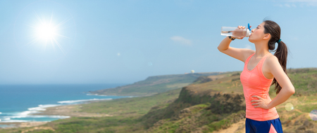 young athlete jogger on the top of the hill holding the bottle drinking water to add energy after running training physical fitness endurance banner with copy space. Standard-Bild