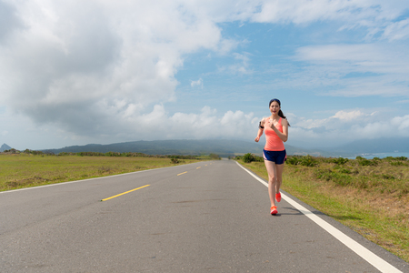 run way: young woman in the beautiful scenery road jogging running workout training endurance in order to personal goals in the morning. Stock Photo