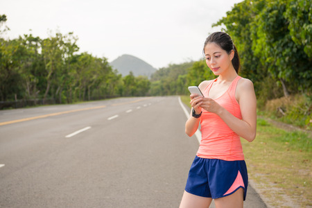 beautiful female jogging runner wearing smartwatch standing on road street using mobile cell phone contact texting with friends after completion marathon game. Stock fotó