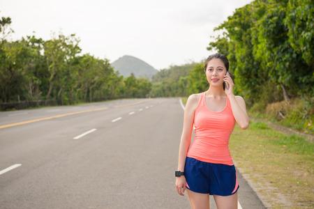 vrouwenloper die zich op weg aan het verzoeken van familie door mobiele smartphone bevindt wanneer zij geschiktheidstraining workout bij de lange straatjogging voltooit. Stockfoto