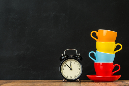 retro small alarm clock on wood texture floor over blackboard wall background in creative studio with four stacked color attractive coffee cups show design copyspace.