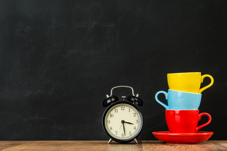stacked colored coffee cups on vintage wood floor with alarm clock equipment showing design inspired copyspace on blackboard wall background in fashion style studio.