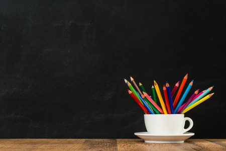 戻って学校に白いコーヒー カップ グループと概念の学習にレインボー鉛筆ショーのたくさん教室黒板壁背景木の机の上。