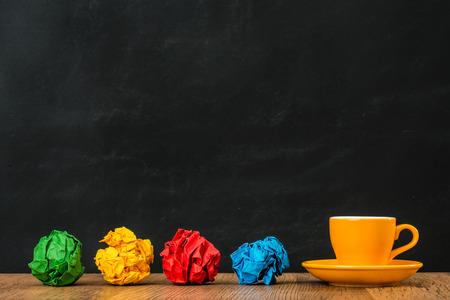 오렌지 세라믹 에스프레소 컵과 컬러 용지 공 무지개 스타일 개념 레트로 디자인와 결합하는 현대적인 스타일을 보여주는 나무 질감 테이블 칠판 배경