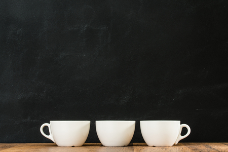 three white coffee cups arranged together placed on retro wood texture floor with black chalkboard wall background in restaurant studio. Stock Photo