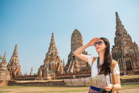 mapa china: young woman in stylish clothes holding city map while standing in Ayutthaya village in Bangkok, Thailand, looking for next station  famous position with Wat Chaiwatthanaram building over copyspace.