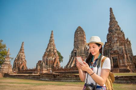 Aziatische vrouw die smartphone zoeken die kijkend kaart van Wat Chaiwatthanaram-park in Ayutthaya, Thailand, texting sms-bericht online op mobiele smartphone voor zaken over copyspace zoeken. Stockfoto