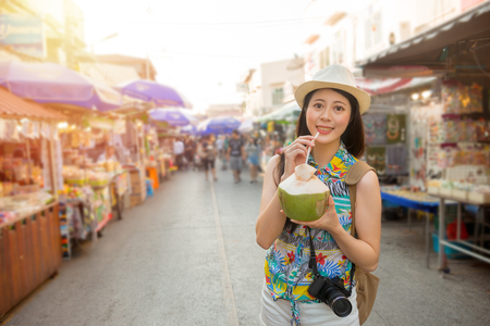 famous female blogger going to Thailand travel tasting local popular coconut water on the Amphawa Floating Market street and take pictures sharing on her personal blog of world travel.