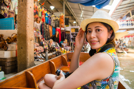 asian women traveler on travel in Thailand wearing hat smiling happy face to camera by floating market during vacation holidays in Damnoen Saduak. Asia holiday and travel vacation concept. Stock Photo