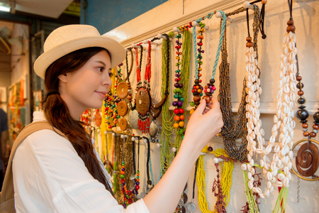 mixed race asian chinese woman travel on the Hong Kong town searching traditional pretty jewelry necklace buying for family as vacation present in local famous vendors.
