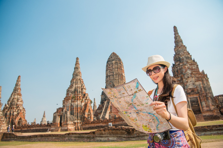 Asian tourist woman with map paper searching for attractions traveling in Ayutthaya town with the Wat Chaiwatthanaram in the background. Young chinese adult visiting the city in Thailand.