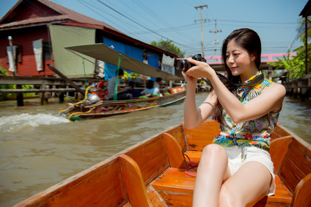 Damnoen Saduak floating market tourist. Young traveler woman holding camera sitting in canal ferry, Beautiful happy smiling mixed race asian chinese woman. Asia holiday and travel vacation concept
