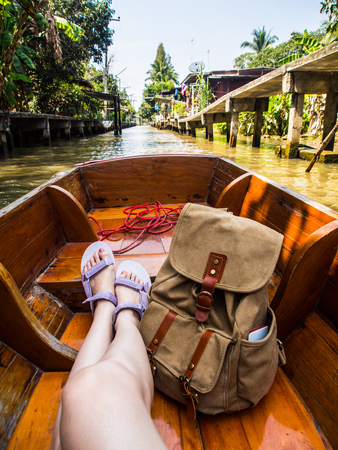 asian woman sitting on canal boat in floating market looking and enjoying river lifestyle view during her wearing sandals with backpack. Asia holiday and travel vacation concept.