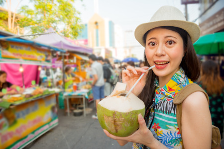 closeup of smiling beautiful woman tourist portrait buy delicious coconut water on travel vacation street outdoor market with all blur stalls background. Banco de Imagens