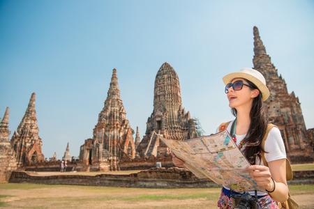 Viaje em Tailândia - mulher asiática do turista com o mapa local que procura por sentidos com a paisagem da excursão de Ayutthaya no fundo e pensando boas coisas no copyspace. Foto de archivo - 83958670