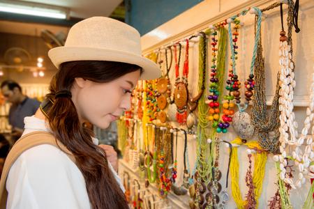 mooie vrouw op de traditionele sieraden accessoires winkel winkel serieus kiezen geschikte ketting voor zichzelf op de reis vakantie van Cebu, Filippijnen populaire straatmarkt.