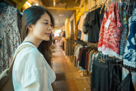 vintage style photography of elegant woman traveler walking on the retro old street shopping with local store shop and looking for colorful clothes in the Thailand vacation trip.