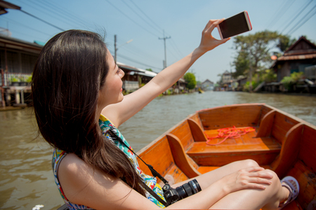 Asian tourist in Damnoen Saduak floating market taking self-portrait photo smiling happy showing with river in background. Travel and tourism concept with beautiful girl travelling bangkok Thailand. Stock Photo