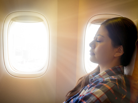 tired brunette casual asian lady napping on comfortable cabin seat while flying traveling with sunshiny from outside sky. Stock Photo