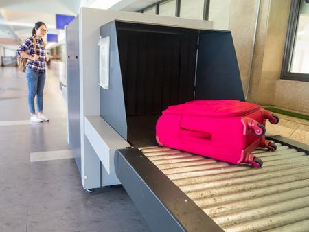 mooie vrouw Chinese wachtende bagage door punt van het controleren van de scanner. Bagage X-ray machineband op de transportband op de luchthaven. Stockfoto