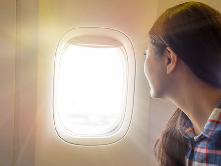 traveler in the airplane. international exchange student sitting at the window of the plane look out sky glare when the plane flying. Foto de archivo