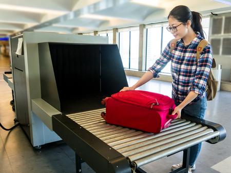 Mooie vrouw chinese zet bagage bij punt van het controleren van de scanner. Bagage X-ray machine band op de transportband op de luchthaven. Selectieve focus